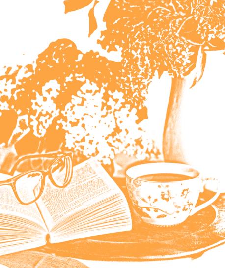 Buch mit Brille und Teetasse auf einem Tisch mit Blumen