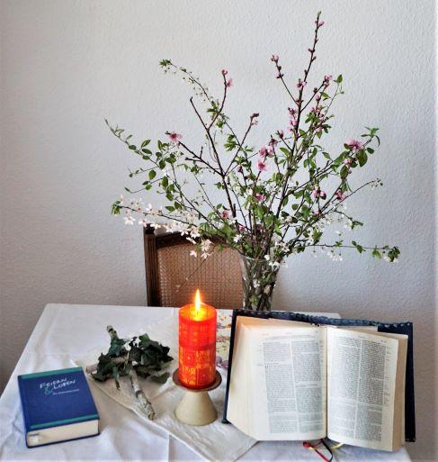 Bibel, Kerze, Gesangbuch und Blumenstrauß auf Tisch